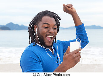 African american guy with dreadlocks listening to music at...