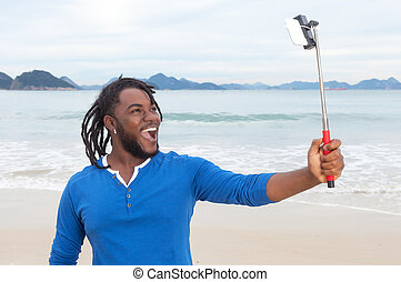 African american guy with dreadlocks at beach taking picture...