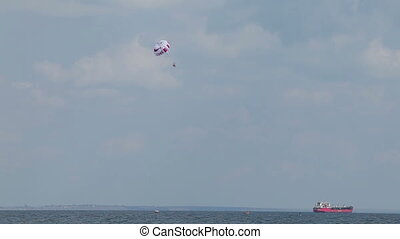 People fly on a parachute over the water