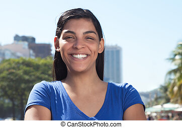 Latin woman with long dark hair in the city looking at...