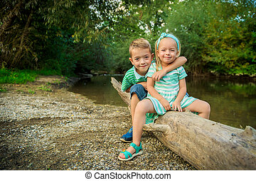 Adorable siblings posing for a portrait, summer outdoors concept
