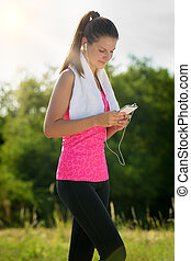 Attractive female taking a break after jogging, holding smartphone
