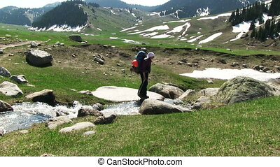 Hiker Crossing A Small River - hiker crossing a small river...
