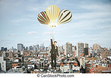 Businessman with baloons above megapolis city concept