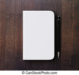 Blank white diary cover and pen on brown wooden table, mock...