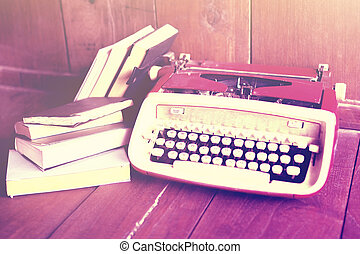 Old style typewriter and books on a wooden floor