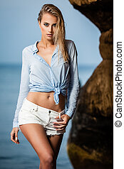 Blue wet shirt - Young woman in wet shirt posing on a sand...