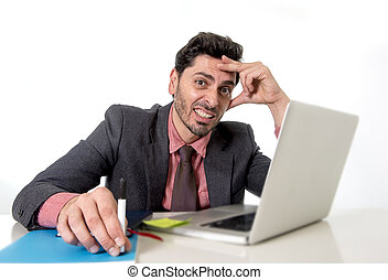 attractive businessman at office desk working on computer laptop looking tired and busy