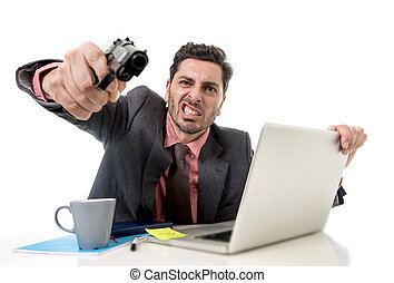 businessman at office desk working on computer laptop pointing gun looking angry and crazy
