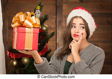 Beautiful girl holding a present near New Year tree -...