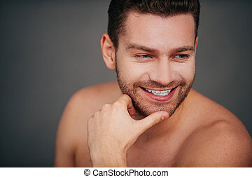 He got candid smile Confident young shirtless man holding...
