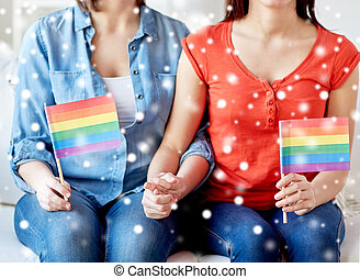 close up of lesbian couple with rainbow flags - people,...