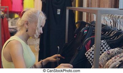 Happy blond woman on shopping in Milan, choice of clothing...