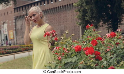 Beautiful blonde in the yellow dress posing standing next to the bushes of blooming roses in Milan