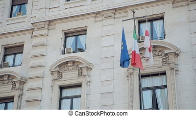 Flags of Milan, Italy and the European Union in the window...