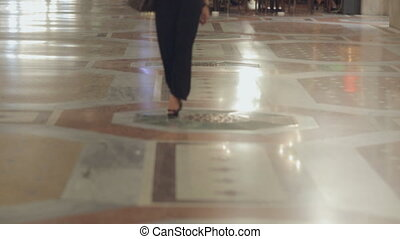 Attractive blonde on high heels and dressed in a long black dress walks in the evening in Milan