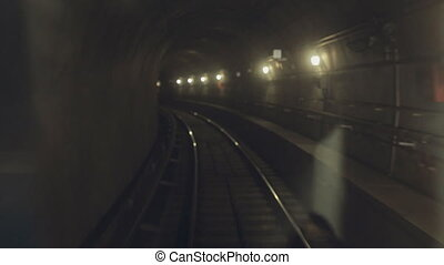 Dark subway located underground , illuminated with lights