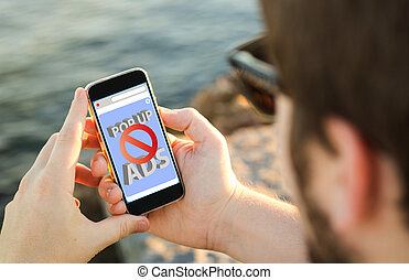 Man using his mobile phone on the coast with ads blocker -...