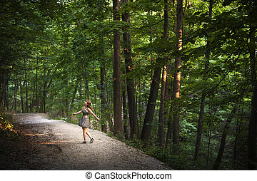 Dancing in forest - Small figure of young woman dancing on...