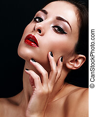 Beautiful makeup woman with bright red lips and black manicured nails on black background. Closeup portrait