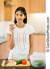 indian woman tasting cucumber - portrait of pretty indian...