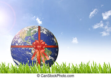 Planet Earth with red ribbon on beautiful green grass nd...