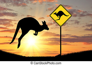 Silhouette of a kangaroo with a baby and a road sign at...