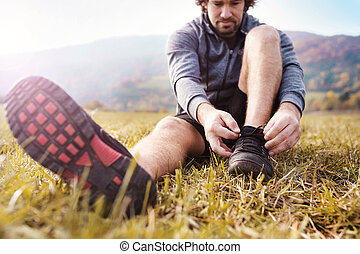 Young man running - Young runner sitting on grass and tying...
