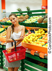 Young woman shopping in a supermarket in the department of fruit and vegetables