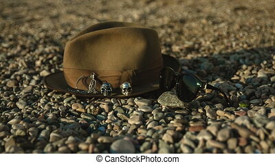hat and sunglasses lying on the pebble beach