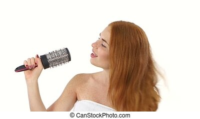 Young girl singing using a brush as a microphone, bathroom -...