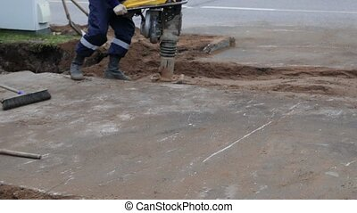 Worker using construction jackhammer on the street. Man with the automatic drill ram sand on the road. Road work. Construction, vibration, close up
