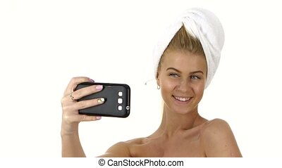 woman with a towel on her head takes selfie. Close up, bathroom