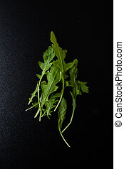rucola - green organic rucola leafs on a black table