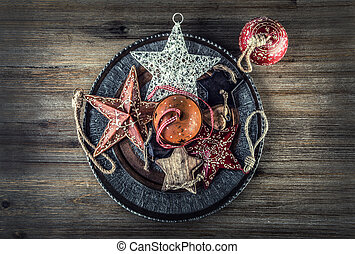 Christmas decorations - stars Jingle bells, candles on wooden table.