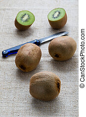kiwi on table cloth - cut and whole kiwi on table cloth with...