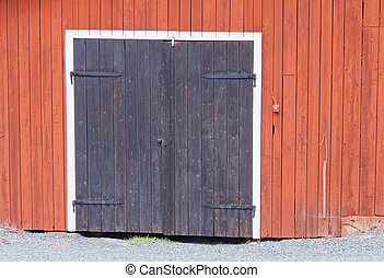 One black door in a red barn wall - One black door with...