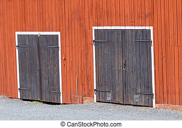 Two black doors in a red barn wall - Two black doors with...