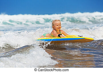 Little child swimming with bodyboard on the sea waves -...