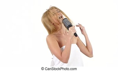 Young girl singing using a brush as a microphone. slow motion, bathroom