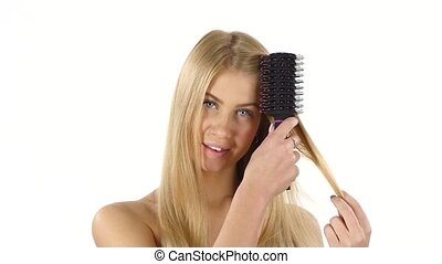 Hair. Beautiful Blond Brushing Her Hair. Hair Care. slow...