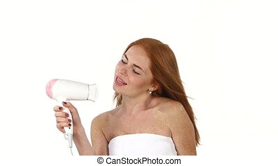 Smiling young Redhead girl singing white hair dryer. slow...
