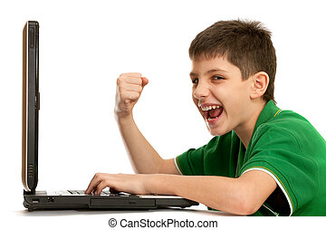 Emotional kid is playing computer game on the laptop - An...