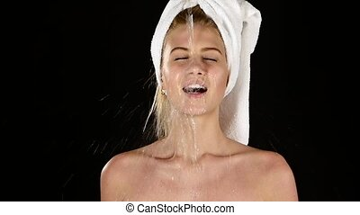 Young female washing her face with clear water. slow motion,...