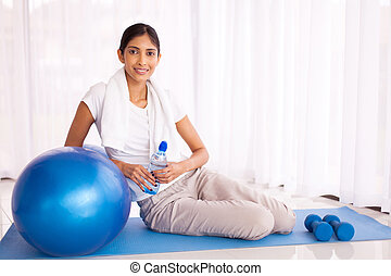 indian woman sitting on mat with exercise ball