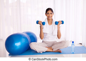 indian girl exercising with dumbbells