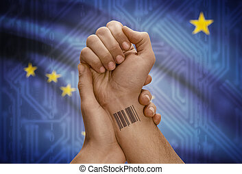 Barcode ID number on wrist of dark skinned person and USA states flags on background - Alaska