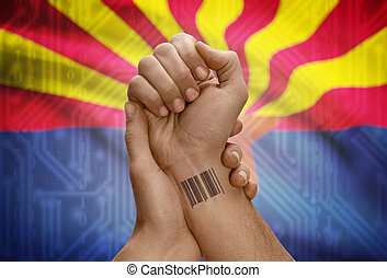 Barcode ID number on wrist of dark skinned person and USA states flags on background - Arizona