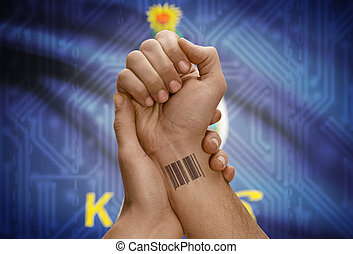 Barcode ID number on wrist of dark skinned person and USA states flags on background - Kansas