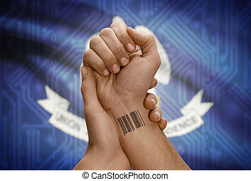 Barcode ID number on wrist of dark skinned person and USA states flags on background - Louisiana
